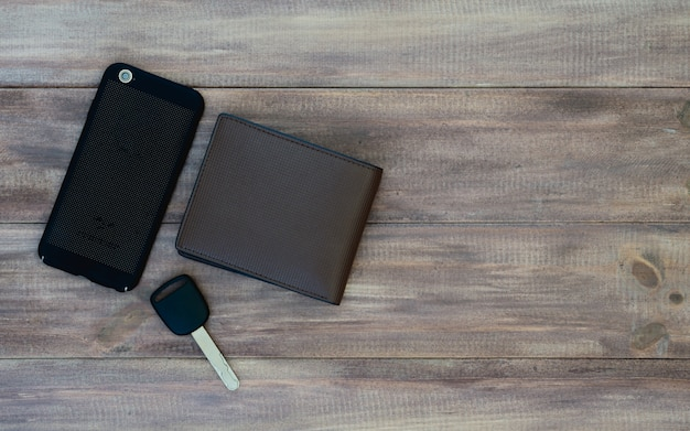 Draufsicht des mannsatzes. geldbörse, autoschlüssel und smartphone auf hölzernem hintergrund.