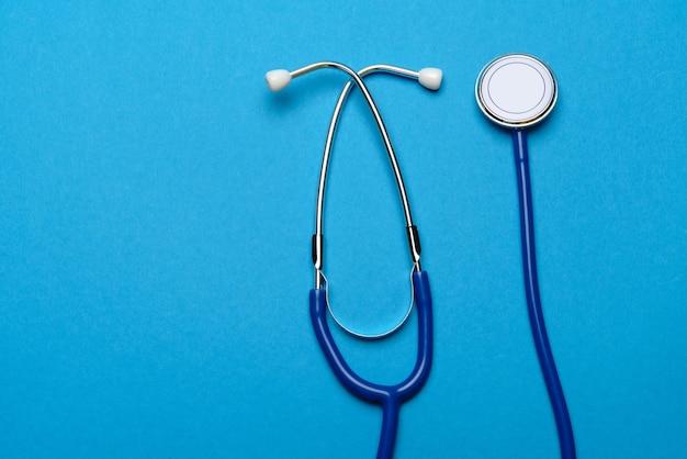 Draufsicht des medizinischen stethoskops auf blauem hintergrund