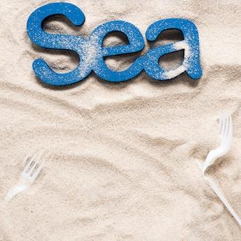 Draufsicht des meeres auf strandsand mit plastikgabeln