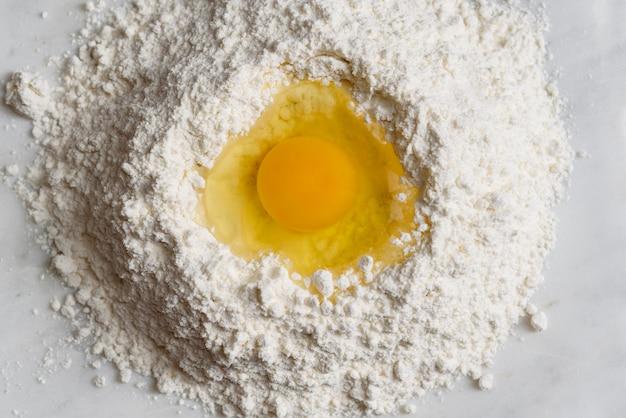 Draufsicht des mehls mit eigelb tp bereiten sich zum kochen vor