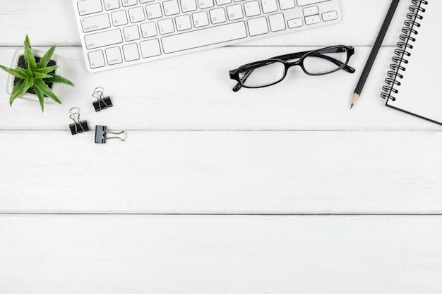 Draufsicht des minimalen schreibtischs mit einem offenen leeren notizbuch und briefpapiereinzelteilen