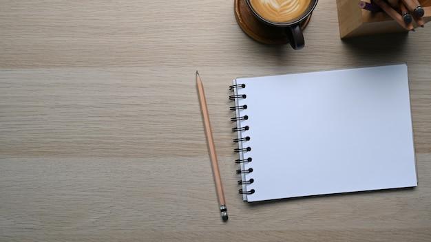 Draufsicht des minimalen schreibtischs mit leerem notizbuch, bleistift