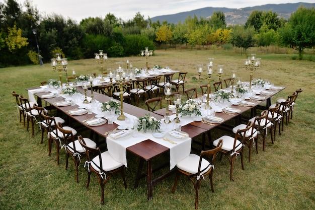 Draufsicht des mit minimalen blumensträußen dekorierten hochzeitsfeier-tisches mit chiavari-sitzen draußen in den gärten mit blick auf die berge