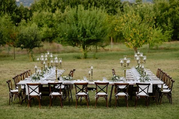 Draufsicht des mit minimalen blumensträußen und kerzen dekorierten hochzeitsfeier-tisches mit chiavari-sitzen draußen in den gärten vor obstbäumen