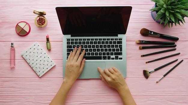 Draufsicht des modebloggerarbeitsbereichs mit laptop- und frauenkosmetik, make-up-werkzeugen und zubehör auf farboberfläche. schönheits- und modekonzept.
