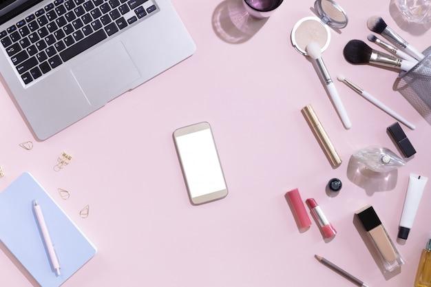 Draufsicht des modells des handys mit weißem leerem kopienraumschirm in der weiblichen hand. flacher laienfrauenarbeitsplatz mit laptop, dekorativem kosmetiksatz, briefpapier und blumen, hartes licht