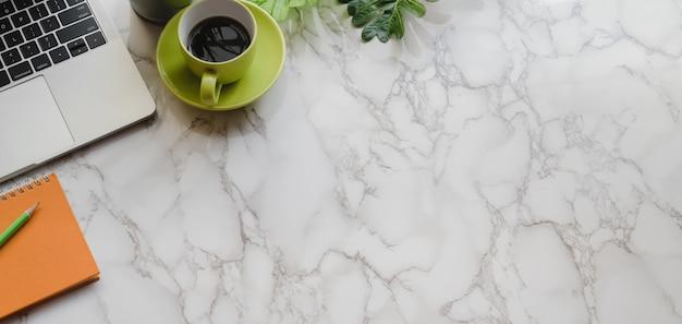 Draufsicht des modernen arbeitsplatzes mit büroartikel und rohkaffeetasse auf marmorschreibtisch