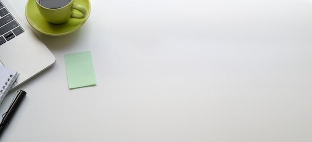 Draufsicht des modernen arbeitsplatzes mit laptop-computer und rohkaffeetasse auf weißer tabelle
