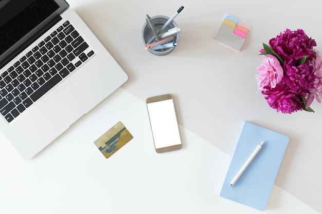 Draufsicht des modeschreibtischs mit kreditkarte für online-zahlung auf laptop-computer oder handy, ebenenlage