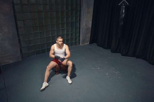 Draufsicht des modischen ernsten jungen muskulösen geschäftsmannes, der weißes ärmelloses hemd, turnschuhe und rote hose trägt, die hände mit bandagen vor dem boxtraining nach arbeitstag im büro kleben