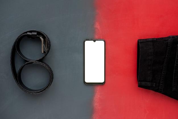 Draufsicht des modischen schwarzen ledergürtels, der schwarzen jeans und des telefons auf grauer und roter oberfläche