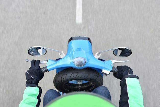 Draufsicht des motorradtaxifahrers auf der fahrt