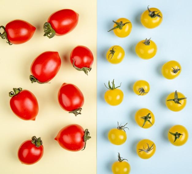 Draufsicht des musters der roten und gelben tomaten auf gelber und blauer oberfläche