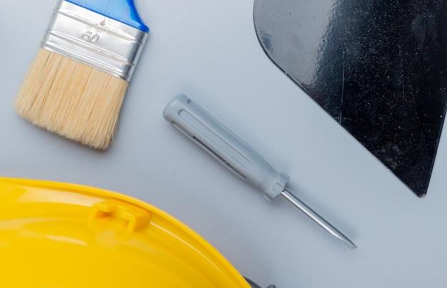 Draufsicht des musters vom satz des bauwerkzeugs als schraubendreher-sicherheitshelm-kittmesser-pinsel auf grauem hintergrund