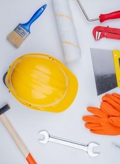 Draufsicht des musters vom satz von bauwerkzeugen als backsteinhammerrohrschlüssel-sicherheitshelm-spachtelmesser-schmerzkontrollpinsel und gabelschlüssel auf weißem hintergrund