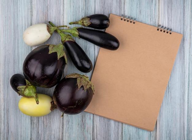 Draufsicht des musters von auberginen und notizblock auf hölzernem hintergrund mit kopienraum