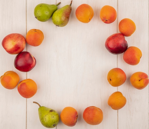 Draufsicht des musters von früchten als pfirsich-aprikose und birne, eingestellt in runder form auf hölzernem hintergrund mit kopienraum