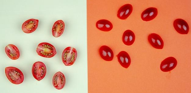 Draufsicht des musters von ganzen und geschnittenen tomaten auf weißer und orange oberfläche