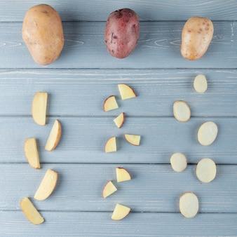 Draufsicht des musters von geschnittenen und ganzen kartoffeln auf hölzernem hintergrund
