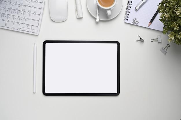 Draufsicht des nachgebildeten digitalen tablets mit leerem bildschirm und büromaterial auf weißem schreibtisch.