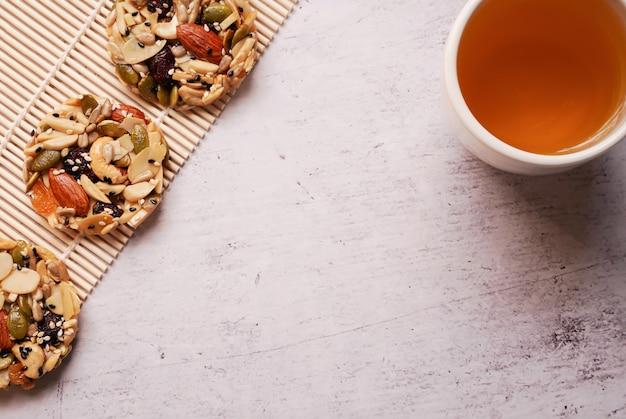 Draufsicht des nachtischs der nuss, der mandel, der trockenen frucht auf der bambusmatte und des heißen chinesischen tees