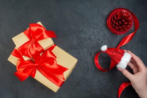 Draufsicht des nadelbaumkegels und der schönen geschenkhand, die weihnachtsmannhut auf dunklem hintergrund hält