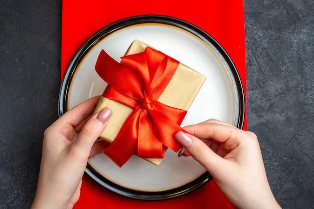 Draufsicht des nationalen weihnachtsmahlzeithintergrundes mit hand, die leere teller mit bogenförmigem rotem band auf einer roten serviette auf schwarzem tisch hält