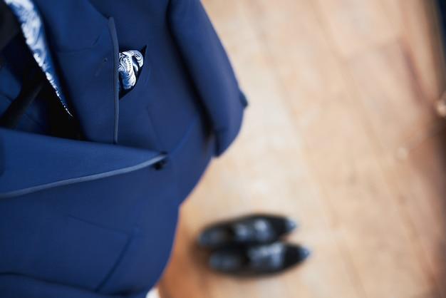 Draufsicht des neuen blauen anzugs und der bindung der hochzeit des bräutigams, die an einem aufhänger hängt