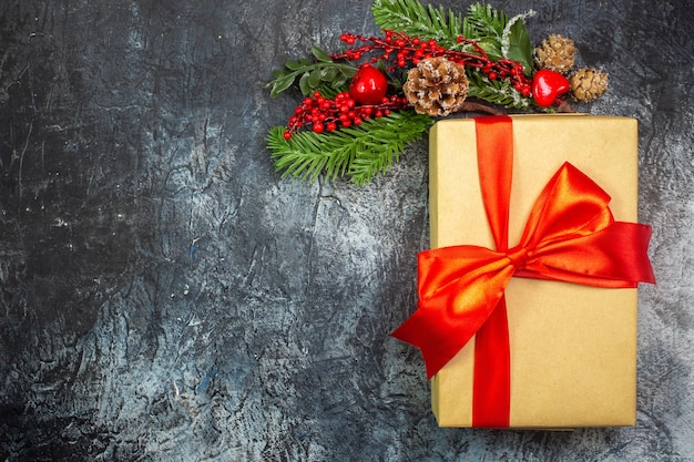 Draufsicht des neujahrsgeschenks mit rotem band und zubehördekorationen auf dunkler oberfläche