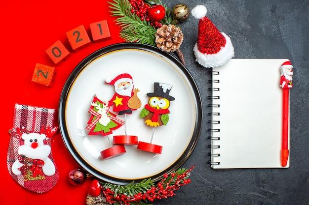 Draufsicht des neujahrshintergrundes mit abendessenplatte-dekorationszubehör tannenzweigen und zahlenweihnachtssocke auf einem roten servietten-notizbuch mit stift auf einem schwarzen tisch