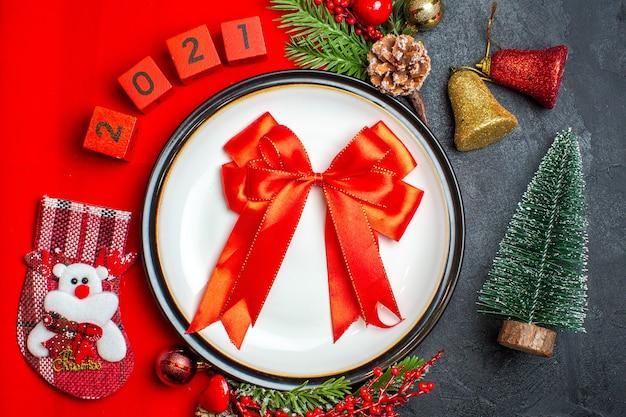Draufsicht des neujahrshintergrundes mit rotem band auf tellerdekorationszubehör tannenzweigen und zahlenweihnachtssocke auf einer roten serviette neben weihnachtsbaum auf einem schwarzen tisch