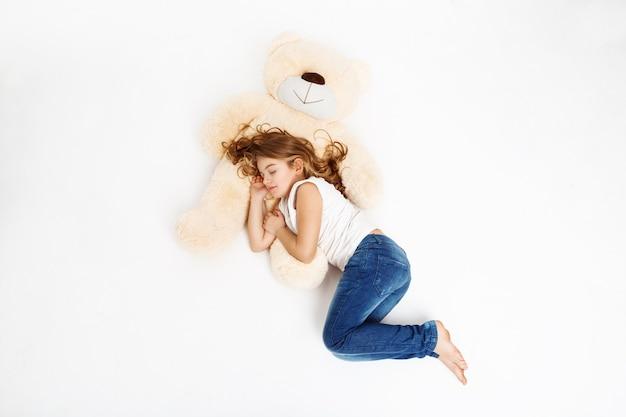 Draufsicht des niedlichen kindes, das auf lieblingsspielzeug schläft.
