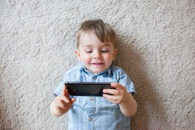 Draufsicht des niedlichen kleinen jungen, der ein bildschirmtelefon hält und bilder zu sich selbst mit smartphone macht.