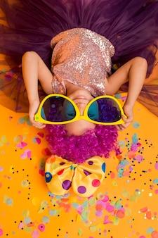 Draufsicht des niedlichen mädchens mit großer sonnenbrille und konfetti