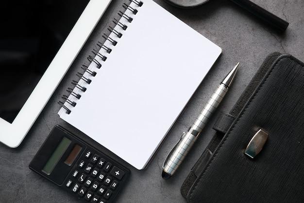 Draufsicht des notizblocks, des digitalen tablets und des stiftes auf schwarzem hintergrund