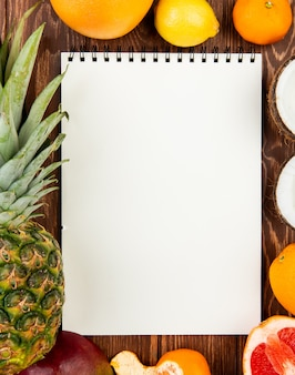 Draufsicht des notizblocks mit ananasorangen-zitronen-mandarinen-kokosnuss-mango-grapefruit herum auf hölzernem hintergrund mit kopienraum