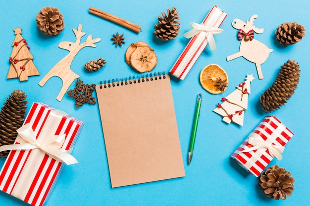 Draufsicht des notizbuches auf dem blau gemacht von den weihnachtsdekorationen.