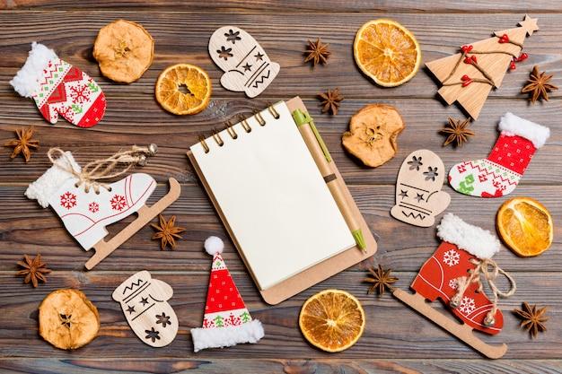 Draufsicht des notizbuches auf hölzernem gemacht von den weihnachtsdekorationen.