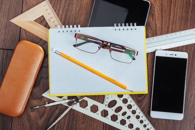 Draufsicht des notizbuches, des briefpapiers, der zeichenwerkzeuge und einiger gläser. improvisieren.