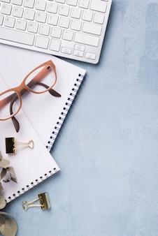 Draufsicht des notizbuches mit getrockneten blättern und gläsern auf schreibtisch
