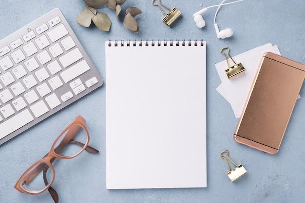 Draufsicht des notizbuches mit gläsern und smartphone auf schreibtisch
