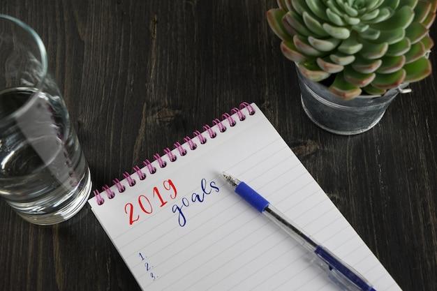 Draufsicht des notizbuches mit zielen des textes 2019 und liste mit kopienraum tun