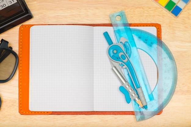Draufsicht des notizbuches mit zirkel und brillen
