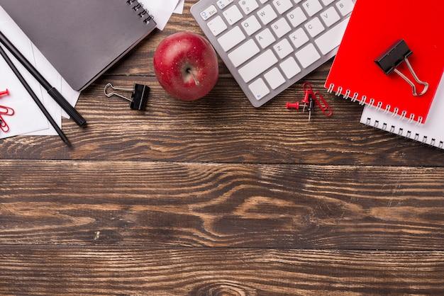 Draufsicht des notizbuches und der tastatur auf hölzernem schreibtisch