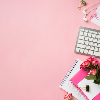 Draufsicht des notizbuches und des blumenstraußes der rosen auf schreibtisch mit exemplarplatz