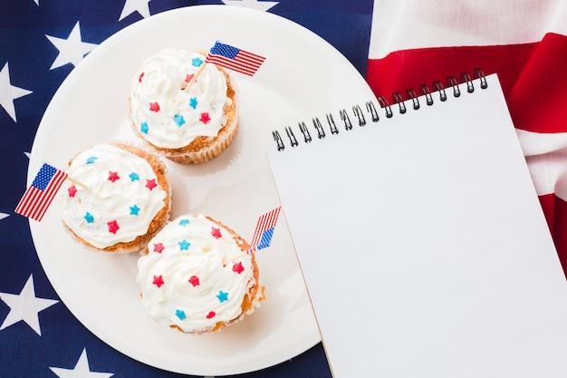 Draufsicht des notizbuchs mit cupcakes und amerikanischer flagge