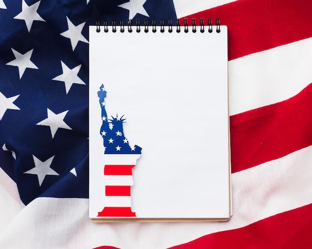 Draufsicht des notizbuchs mit freiheitsstatue und amerikanischer flagge