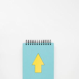 Draufsicht des notizbuchs mit gelbem pfeil