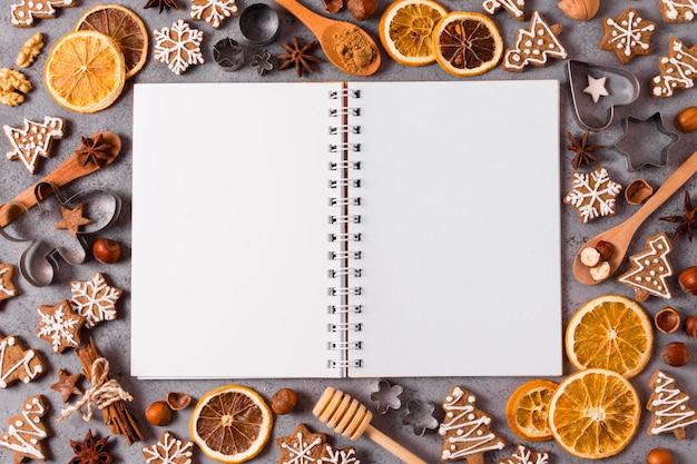 Draufsicht des notizbuchs mit getrockneten zitrusfrüchten und lebkuchen