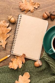 Draufsicht des notizbuchs mit herbstlaub und kaffee
